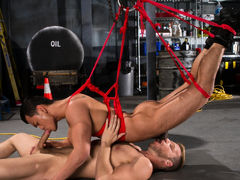 Dom top Brian Bonds releases his sub, Eli Lewis, from his cage for some intense, deep cocksucking. Eli's chest is bound in a red rope harness, which Brian attaches to a suspended ring. Gathering larger amount rope, Brian connects Eli's legs to the ring an
