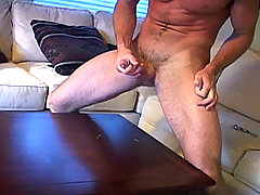First slowly undresses while stroking his hard rock cock!
